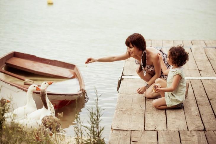 mama e hija alimentan un pato en el lago